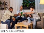 Купить «happy male friends drinking beer at home at night», фото № 33369008, снято 28 декабря 2019 г. (c) Syda Productions / Фотобанк Лори
