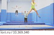 Купить «View through yellow safety net of positive young men and woman training in trampoline center», видеоролик № 33369340, снято 2 апреля 2020 г. (c) Яков Филимонов / Фотобанк Лори