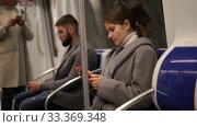 Купить «Man and woman using phone inside subway», видеоролик № 33369348, снято 11 ноября 2019 г. (c) Яков Филимонов / Фотобанк Лори