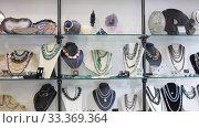 Купить «Close up of natural stone bead necklaces in jewelry shop», видеоролик № 33369364, снято 31 октября 2019 г. (c) Яков Филимонов / Фотобанк Лори