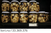 Купить «Closed glass jars with popular in Catalonia pickled young fredolics (tricholoma terreum mushrooms) on shelf in store», видеоролик № 33369376, снято 31 марта 2020 г. (c) Яков Филимонов / Фотобанк Лори