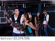 Купить «Triumphing team of laser tag winners guy and girl in foreground and losers team», фото № 33374596, снято 27 августа 2018 г. (c) Яков Филимонов / Фотобанк Лори