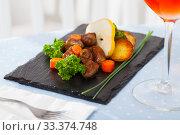 Купить «Braised chicken hearts with baked potatoes, carrots, fresh pear», фото № 33374748, снято 28 марта 2020 г. (c) Яков Филимонов / Фотобанк Лори