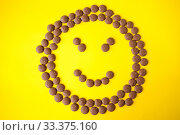 Купить «Drops of milk chocolate are laid out in a circle and a smile on a yellow background», фото № 33375160, снято 14 марта 2020 г. (c) Катерина Белякина / Фотобанк Лори