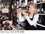 Купить «Attentive female winemaker holding glass of wine», фото № 33375696, снято 9 апреля 2020 г. (c) Яков Филимонов / Фотобанк Лори