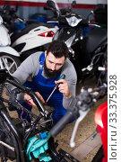Worker repairing motorbike. Стоковое фото, фотограф Яков Филимонов / Фотобанк Лори