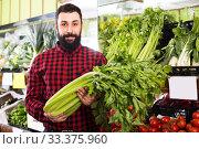 Adult male seller offering celery in shop. Стоковое фото, фотограф Яков Филимонов / Фотобанк Лори