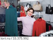 Купить «Female shopper examining turtleneck sweaters in women's cloths shop», фото № 33375992, снято 7 февраля 2017 г. (c) Яков Филимонов / Фотобанк Лори