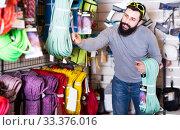 Купить «joyous male customer examining climbing equipment in sports equipment store», фото № 33376016, снято 24 февраля 2017 г. (c) Яков Филимонов / Фотобанк Лори