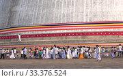 Паломники у подножия древней дагобы Руванвелисия. Анурадхапура, Шри-Ланка (2020 год). Редакционное видео, видеограф Виктор Карасев / Фотобанк Лори