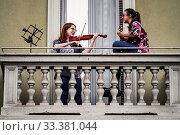 Купить «Musicians play simultaneously from their windows and balconies during the musical flash mob to combat isolation due Coronavirus emergency, Milan ,ITALY-13-03-2020.», фото № 33381044, снято 13 марта 2020 г. (c) age Fotostock / Фотобанк Лори