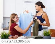 Купить «Two young positive girlfriends looking new clothes at table and sharing», фото № 33386636, снято 29 августа 2018 г. (c) Яков Филимонов / Фотобанк Лори