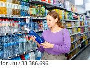 Купить «Young positive woman purchasing water in bottles in grocery store», фото № 33386696, снято 11 июля 2020 г. (c) Яков Филимонов / Фотобанк Лори