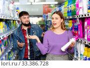 Купить «Portrait of positive young woman and man choosing liquid laundry detergents during shopping at supermarket», фото № 33386728, снято 4 апреля 2020 г. (c) Яков Филимонов / Фотобанк Лори