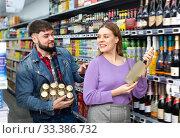 Купить «Adult man and woman choosing bottle of cava», фото № 33386732, снято 4 июля 2020 г. (c) Яков Филимонов / Фотобанк Лори