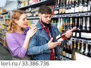 Купить «Glad man and woman choosing bottle of cava», фото № 33386736, снято 28 марта 2020 г. (c) Яков Филимонов / Фотобанк Лори