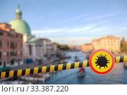 Купить «Warning sign with Coronavirus molecule on a police line on the blurred background of Grand Canal in Venice, Italy.», фото № 33387220, снято 22 июля 2014 г. (c) Ярослав Данильченко / Фотобанк Лори