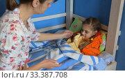 Купить «Мама смотрит температуру на электронном термометре у заболевшей дочки», видеоролик № 33387708, снято 17 марта 2020 г. (c) Иванов Алексей / Фотобанк Лори