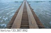 Купить «Вид на причал уходящий далеко в море, волны накатывают на песчаный берег», видеоролик № 33387992, снято 18 марта 2020 г. (c) Иванов Алексей / Фотобанк Лори