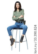Купить «A young woman in jeans, boots and a khaki shirt is sitting on a high chair. Isolated on white.», фото № 33390824, снято 11 января 2020 г. (c) Serg Zastavkin / Фотобанк Лори