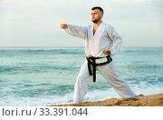 Купить «Guy doing karate poses at sunset sea shore», фото № 33391044, снято 19 июля 2017 г. (c) Яков Филимонов / Фотобанк Лори