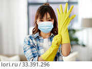 Купить «asian woman in protective mask and rubber gloves», фото № 33391296, снято 13 апреля 2019 г. (c) Syda Productions / Фотобанк Лори