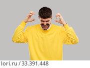 Купить «angry young man in yellow sweatshirt over grey», фото № 33391448, снято 22 февраля 2020 г. (c) Syda Productions / Фотобанк Лори