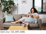 smiling young woman eating cake at home. Стоковое фото, фотограф Syda Productions / Фотобанк Лори