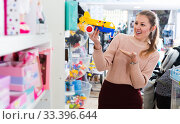 Купить «Woman buying plastic toys», фото № 33396644, снято 19 декабря 2017 г. (c) Яков Филимонов / Фотобанк Лори