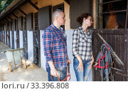 Smiling couple holding a surcingle and feeding a horse at stable outdoor. Стоковое фото, фотограф Яков Филимонов / Фотобанк Лори