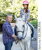 Купить «Man trainer teach to female while riding horse at ranch», фото № 33396816, снято 4 июля 2018 г. (c) Яков Филимонов / Фотобанк Лори