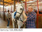 Купить «Mature positive man farmer standing with white horse at stabling», фото № 33396820, снято 4 июля 2018 г. (c) Яков Филимонов / Фотобанк Лори