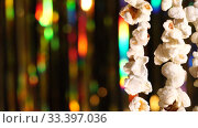 Купить «Vertically hanging garlands of popcorn for sports and movie news. On background dynamic gold background in shining lights and sparkling particles. 4K close up video», видеоролик № 33397036, снято 1 апреля 2020 г. (c) Dmitry Domashenko / Фотобанк Лори