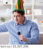 Купить «Funny man singing songs in karaoke at home», фото № 33397296, снято 29 марта 2017 г. (c) Elnur / Фотобанк Лори