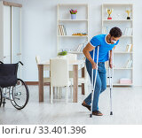 Купить «Young man recovering after surgery at home with crutches and a w», фото № 33401396, снято 26 июля 2017 г. (c) Elnur / Фотобанк Лори