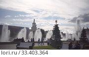 Купить «People walk in VDNH park. Pavilion 58 Agriculture, fountain Stone Flower», видеоролик № 33403364, снято 6 июля 2019 г. (c) Ирина Мойсеева / Фотобанк Лори