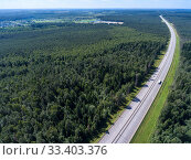 Купить «Wide straight toll highway M-11 passing in forests. View from above. The Moscow-Saint Petersburg motorway designed as the M11 Neva is in Russia», фото № 33403376, снято 31 июля 2018 г. (c) Кекяляйнен Андрей / Фотобанк Лори