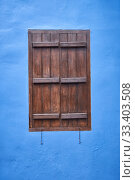 The window with the brown shutter in the blue wall. Cyprus (2018 год). Стоковое фото, фотограф Serg Zastavkin / Фотобанк Лори