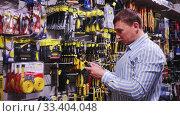 Купить «Portrait of male in hardware store buying goods», видеоролик № 33404048, снято 8 апреля 2020 г. (c) Яков Филимонов / Фотобанк Лори