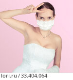 Fashionable Bride in veil dress and lace protective medical mask, posing on a pink background. Стоковое фото, фотограф katalinks / Фотобанк Лори