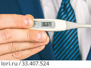 Купить «A man in a suit and tie holds in his hands an electronic thermometer with temperature», фото № 33407524, снято 18 марта 2020 г. (c) katalinks / Фотобанк Лори