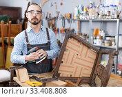 Купить «Craftsman repairing antique furniture», фото № 33408808, снято 19 ноября 2018 г. (c) Яков Филимонов / Фотобанк Лори