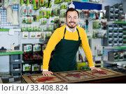 Купить «Seller displaying various items in garden equipment shop», фото № 33408824, снято 2 марта 2017 г. (c) Яков Филимонов / Фотобанк Лори