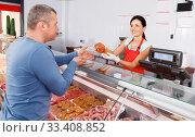 Купить «Smiling seller offering customer different sausages», фото № 33408852, снято 22 июня 2018 г. (c) Яков Филимонов / Фотобанк Лори