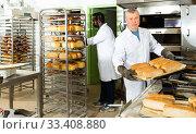 Successful baker spreads freshly baked bread on a pallet. Стоковое фото, фотограф Яков Филимонов / Фотобанк Лори