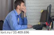 Купить «Молодой человек сильно задумался сидя перед монитором в домашней остановке», видеоролик № 33409696, снято 22 марта 2020 г. (c) Иванов Алексей / Фотобанк Лори