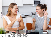 Купить «Smiling young girlfriend doing make-up at table in home», фото № 33409940, снято 2 августа 2018 г. (c) Яков Филимонов / Фотобанк Лори