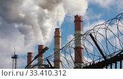 Купить «Factory chimneys smoke thick smoke and steam behind a fence with barbed wire», видеоролик № 33410312, снято 22 марта 2020 г. (c) Алексей Кузнецов / Фотобанк Лори