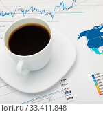 Купить «Coffee cup over world map and market charts», фото № 33411848, снято 4 апреля 2020 г. (c) age Fotostock / Фотобанк Лори