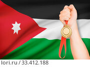 Sportsman holding gold medal with flag on background - Hashemite Kingdom of Jordan. Стоковое фото, фотограф Zoonar.com/Siarhei Tsalko / age Fotostock / Фотобанк Лори
